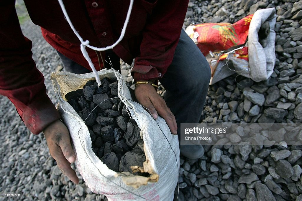 A villager ties up a bag of coals picked out from gangue stockpiles at a coal-chosen factory on August 11, 2006 in Chifeng of Inner Mongolia Autonomous Region, China. Pingzhuang Coal Groups Company, including six open pit coal mines, produces 10 million tons mine per year. Reportedly, in the first four months of this year, China's coal consumption rose by 13.8 percent over the same period of last year, and coal price is expected to go up steadily with the factors of environment, safety and resources included in the cost of coal production.