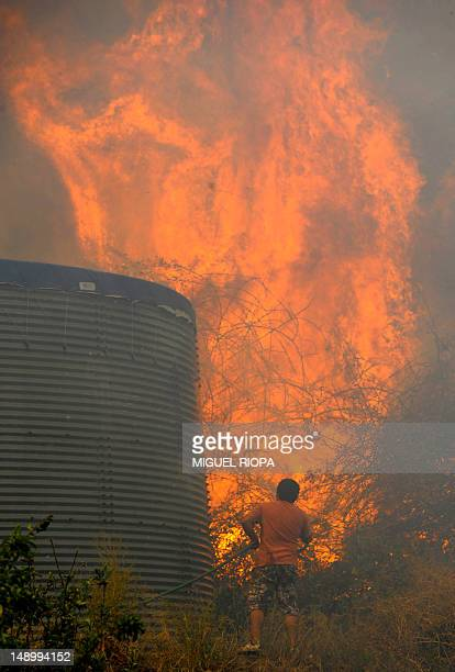A villager tries to extinguish a wildfire near the houses in Assomada on Madeira Island on July 21 2012 The More than 1000 fire fighters and rescuers...
