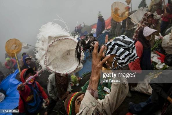A villager try to catch a chicken offerings thrown by Hindu worshippers at the crater of Mount Bromo during the Yadnya Kasada Festival at crater of...