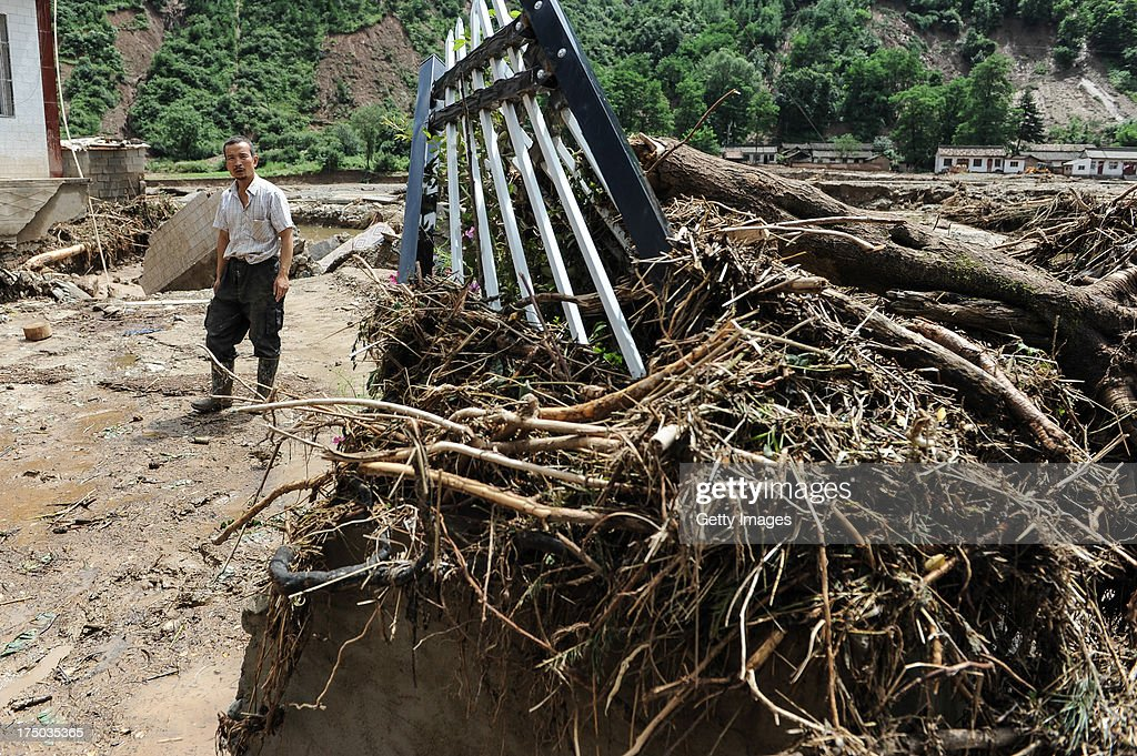 A villager walks past a collapsed house on July 29, 2013 in Tianshui, China. At least 24 people were killed, with one person still missing, after rainstorm-triggered floods and landslides hit many areas of Tianshui city recently.