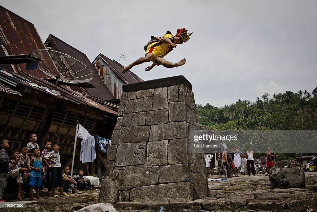 A villager wearing traditional costume jumps over a stone in front of their ancient houses in Orahili Fau village on February 24, 2013 in Nias Island, Indonesia. Stone Jumping is a traditional ritual, with locals leaping over large stone towers, which in the past resulted in serious injury and death. Stone jumping in Nias Island was originally a tradition born of the habit of inter tribal fighting on the island of Nias.