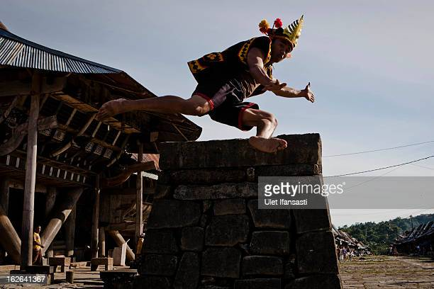 A villager wearing traditional costume jumps over a stone in front of their ancient houses in Bawomataluwo village on February 22 2013 in Nias Island...