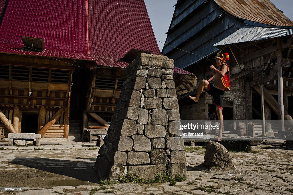 A villager wearing traditional costume jumps over a stone in front of their ancient houses in Bawomataluwo village on February 22, 2013 in Nias Island, Indonesia. Stone Jumping is a traditional ritual, with locals leaping over large stone towers, which in the past resulted in serious injury and death. Stone jumping in Nias Island was originally a tradition born of the habit of inter tribal fighting on the island of Nias.