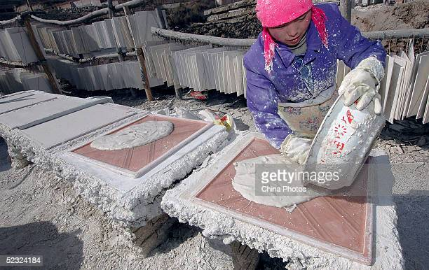 A villager works at her plasterboard workshop on March 8 2005 in Huzhu County of Qinghai Province China The national legislature's annual session has...