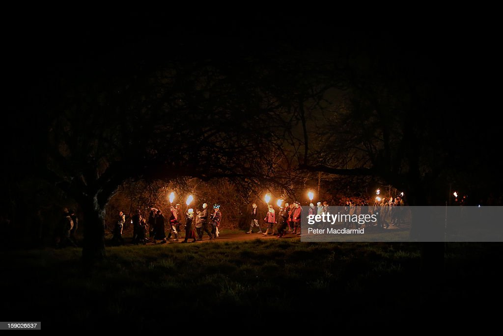 Villagers and Morris Men head back to the farm through the orchard after the Apple Howling ceremony at Old Mill Farm on January 5, 2013 in Bolney, England. In this ancient ritual villagers surround the oldest and largest tree in the orchard and evil spirits are driven out and good spirits are encouraged to produce a bountiful apple crop for the following year's cider drink.