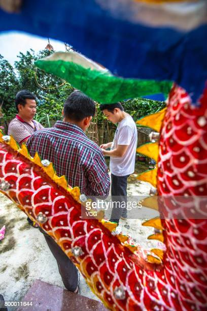 Villagers bundle up a dragon with bamboo frames on June 19 2017 in Meizhou Guangdong Province of China The fire dragon dance of Puzhai Town at...
