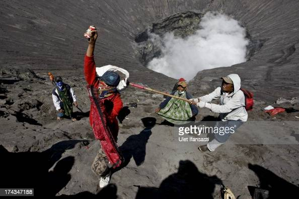 Villagers catch offerings thrown by Hindu worshippers at the crater of Mount Bromo during the Yadnya Kasada Festival at crater of Mount Bromo on July...