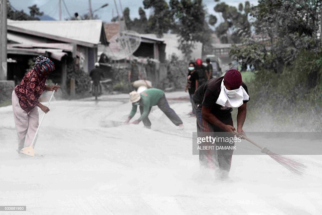 Villagers clean up volcanic ash that has accumulated on the streets, in Karo district, North Sumatra province, on May 24, 2016, after the eruption of Mount Sinabung. Indonesian rescuers searched for survivors in scorched villages and devastated farmlands after a volcano erupted in clouds of searing ash and gas, killing seven and leaving others fighting life-threatening burns. / AFP / ALBERT