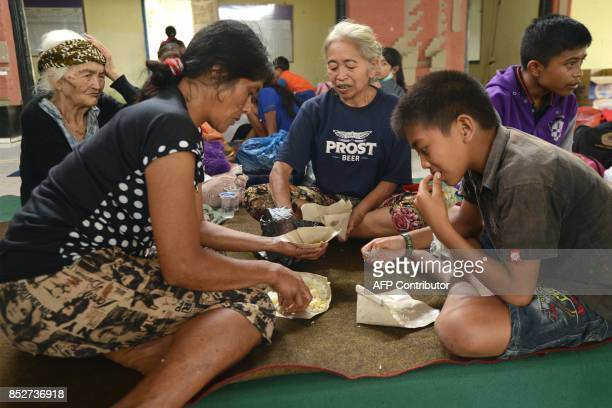 Villagers eat at an evacuation centre in Karangasem on the Indonesian resort island of Bali on September 24 2017 Authorities have raised alert levels...