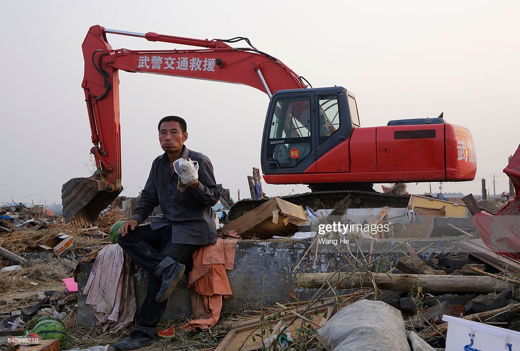 Villagers eat dinner in front of rescue machinery in Beichen Village of Chenliang Township in Funing, Yancheng, east China's Jiangsu Province on June 25, 2016. A total of 98 people were killed after severe storms in several towns in Jiangsu on Thursday, local rescue headquarters said on Friday. About 846 people sustained injuries, 200 of whom were seriously wounded, it said. More than 8,600 houses, two elementary schools and eight factory buildings were damaged in the counties of Funing and Sheyang, and parts of Yancheng City along the eastern coast of China on June 25, 2016 in Yancheng, China.