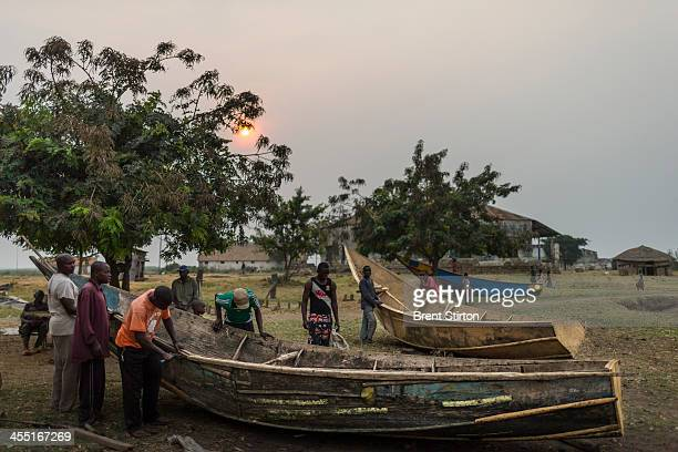 Villagers fix a boat in Vitshumbi Fishing village on the Southern shores of Lake Edward on July 27 2013 in Vitshumbi DR Congo The villagers depend on...