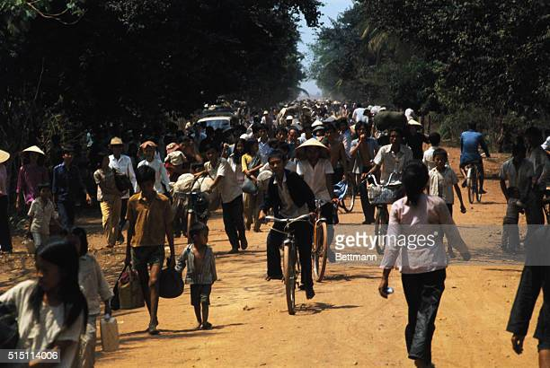 Villagers flee down highway as Communists advance in Dau Tieng 35 miles north of Saigon Blownup bridges blocked 3/19 the escape route for a convoy of...