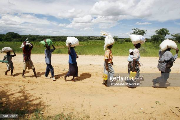 Villagers head home from a school in Chirumanzu district 250 kms from the Zimbabwean capital Harare on January 15 2009 after receiving food rations...