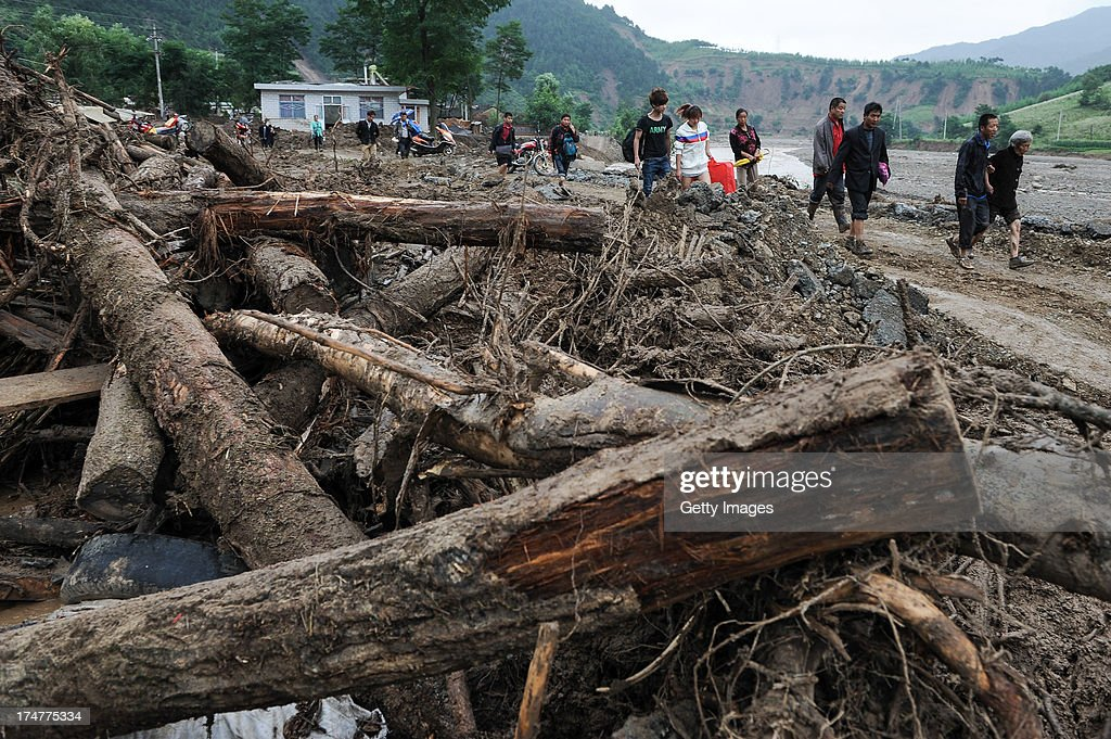 Villagers head to a shelter on July 28, 2013 in Tianshui, China. At least 22 people were killed and three others missing after rainstorm-triggered floods and landslides hit many places of Tianshui city recently.