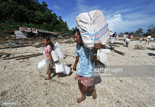 Villagers help to unload relief at Tumalei village in Metawai islands West Sumatra on October 31 2010 six days after a 77magnitude quaketriggered...