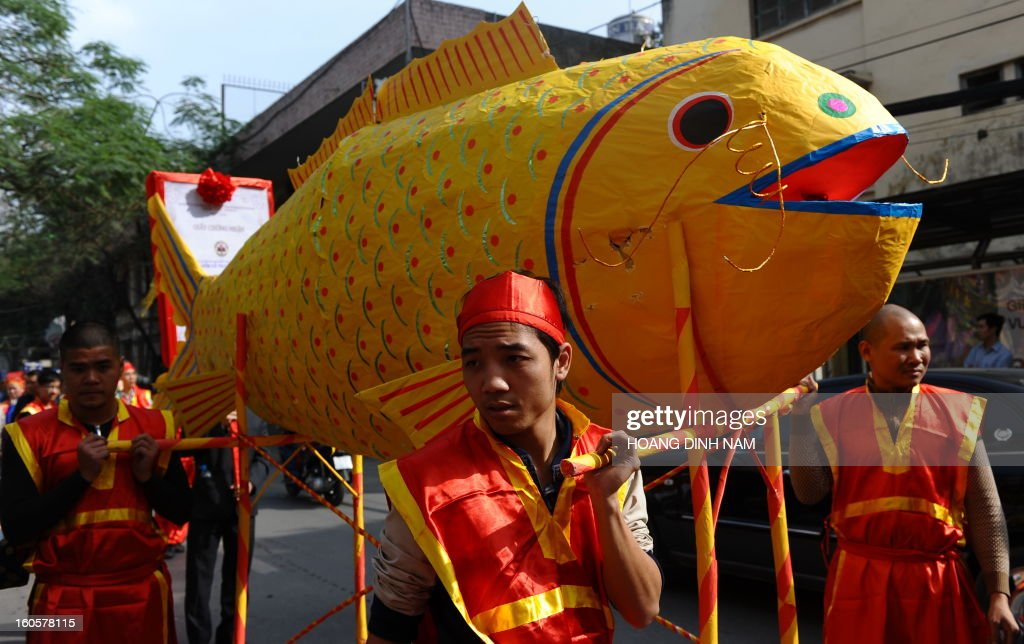 Villagers in festive dress carry a big paper-made carp during a procession to mark the 'Kitchen God Day', part of Lunar New Year or Tet celebrations by Vietnamese, in dowtown Hanoi on February 3, 2013. Vietnamese believe that Tet marks the time when the Kitchen God reports on their family to the Jade Emperor on the 23rd day of the 12th lunar month, meaning a week before Tet. On that day families usually burn gold leaf paper and offer live carp for him to ride. AFP PHOTO / HOANG DINH Nam