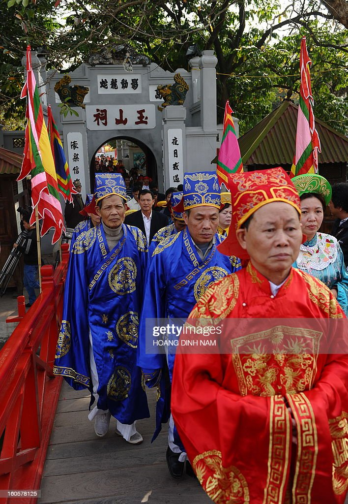 Villagers in festive dress leave a temple during a procession to mark 'Kitchen God Day', part of Lunar New Year or Tet celebrations by Vietnamese, in dowtown Hanoi on February 3, 2013. Vietnamese believe that Tet marks the time when the Kitchen God reports on their family to the Jade Emperor on the 23rd day of the 12th lunar month, meaning a week before Tet. On that day families usually burn gold leaf paper and offer live carp for him to ride. AFP PHOTO / HOANG DINH Nam