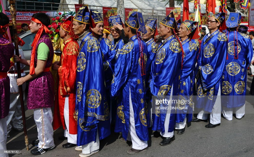 Villagers in festive dress march during a procession to mark 'Kitchen God Day', part of Lunar New Year or Tet celebrations by Vietnamese, in dowtown Hanoi on February 3, 2013. Vietnamese believe that Tet marks the time when the Kitchen God reports on their family to the Jade Emperor on the 23rd day of the 12th lunar month, meaning a week before Tet. On that day families usually burn gold leaf paper and offer live carp for him to ride. AFP PHOTO / HOANG DINH Nam