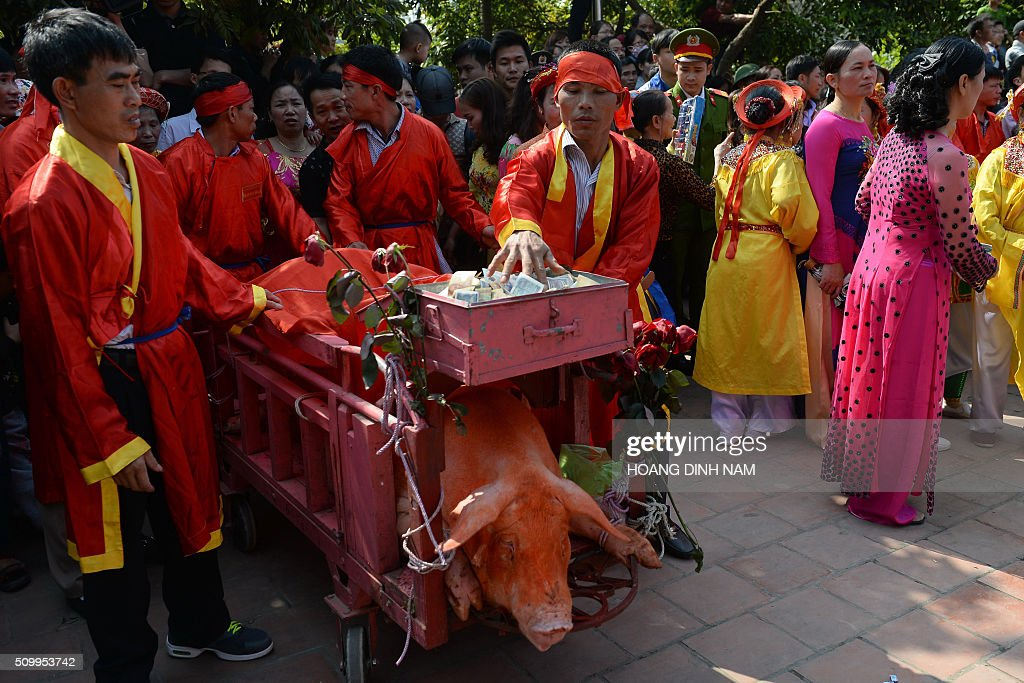 Villagers in red festive dress push a cart with a sacrificial pig at the traditional pig-slaughter festival in Nem Thuong village in the northern province of Bac Ninh on February 13, 2016. Local authorities and villagers performed this year's ritualistic pig slaughter, which takes place on the sixth day of the Lunar New Year, out of public view following fierce criticism from animal rights groups. AFP PHOTO / HOANG DINH Nam / AFP / HOANG DINH NAM