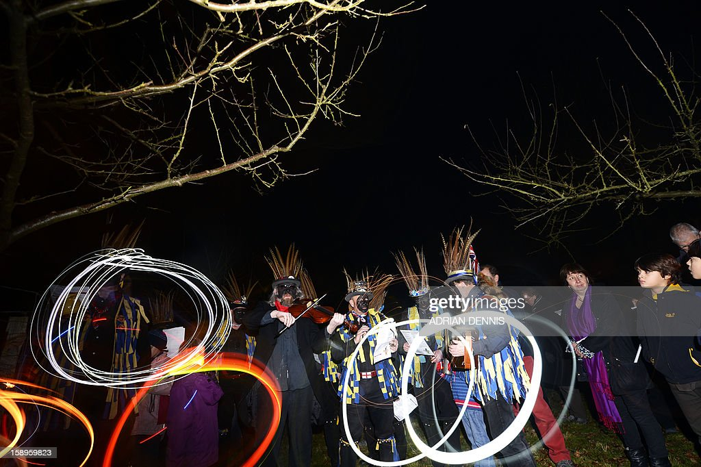 Villagers join the Hook Eagle Morris Men in the orchard during the annual Wassail night in Hartley Wintney, 40 miles (64 Kilometers) west of London, on January 4, 2013. The event, held near to twelfth night, celebrates both the passing of Christmas and the future good health of the fruit trees. Traditionally the custom involved the local farm workers visiting the orchard after dark with shotguns, horns, food and a large pail of cider. They would make a loud noise to raise the Sleeping Tree Spirit and to scare off demons. Cider would be poured over the roots and pieces of toast placed in the branches as a gift to the spirit of the tree. The wassail song is sung as a blessing or charm to bring fruitfulness or even in admonishment not to fail in the upcoming year. AFP PHOTO / ADRIAN DENNIS