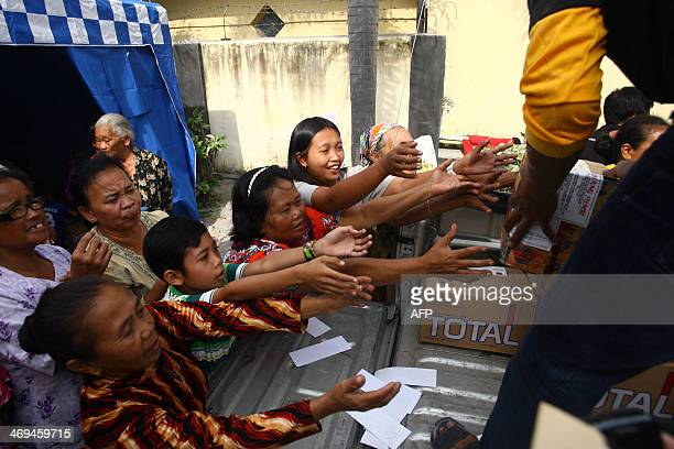 Villagers line up for relief at a shelter in Kediri East Java on February 15 2014 following the volcanic eruption of Mouth Kelud in East Java on...