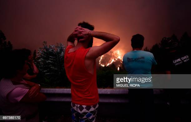 TOPSHOT Villagers look at flames during a wildfire near the village of Mega Fundeira on June 18 2017 Portugal declared three days of national...