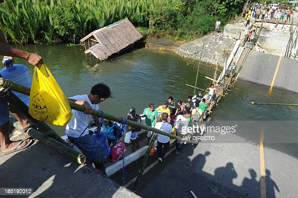 Villagers of Maribojoc Bohol island central Philippine use bamboo ladders to cross a bridge on October 18 that was toppled by the 71 magnitude quake...