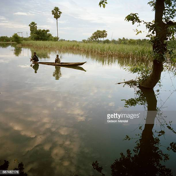 Villagers paddle a canoe through a flooded sugar cane fields near Motihari in the east Champaran district This is in the province of Bihar which was...