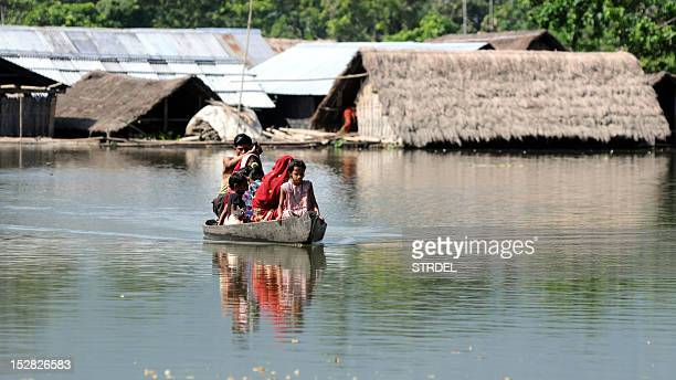 Villagers paddle their boat near submerged houses in a village near Kaziranga National Park on September 27 2012 Rains hampered a military air...