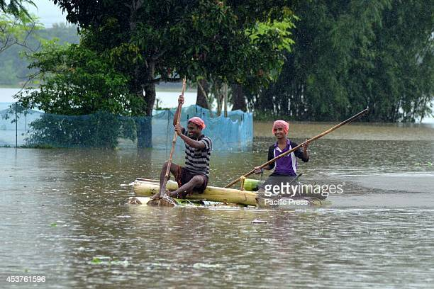 Villagers paddles a banana raft to higher places that are not flooded at Amoni village in Nagaon 180km East of Guwahati Due to heavy rainfall in...