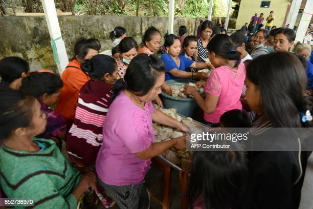 Villagers prepare food at an evacuation centre in Karangasem on the Indonesian resort island of Bali on September 24 2017 Authorities have raised...