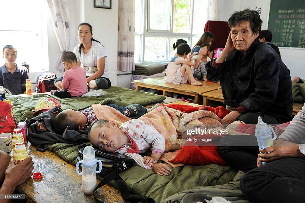 Villagers rest in a shelter on July 29, 2013 in Tianshui, China. At least 24 people were killed, with one person still missing, after rainstorm-triggered floods and landslides hit many areas of Tianshui city recently.