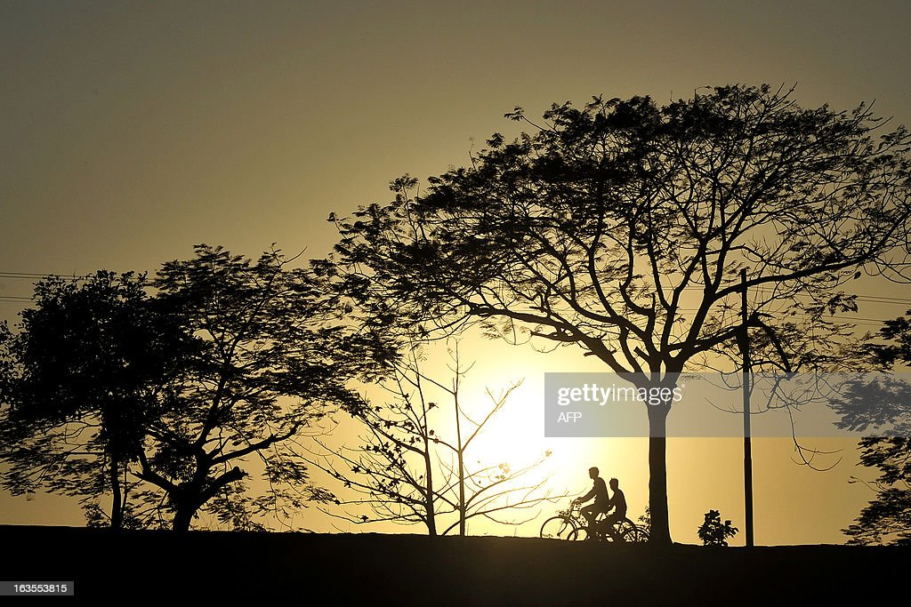 Villagers ride their bicycles during sunset near an agricultural field at Arial village near Allahabad on March 12, 2013. Agriculture contributes about 15 percent to India's gross domestic product but only 40 percent of farms are irrigated. AFP PHOTO/ SANJAY KANOJIA
