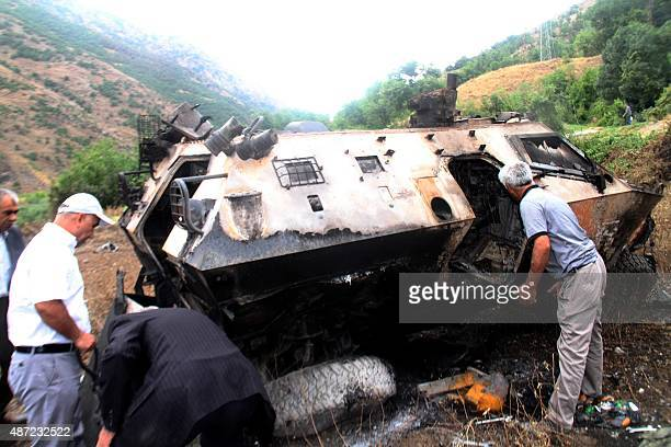 Villagers search for the bodies of Turkish soldiers inside a destroyed armoured vehicle near Daglica District southeastern Turkey on September 7 2015...