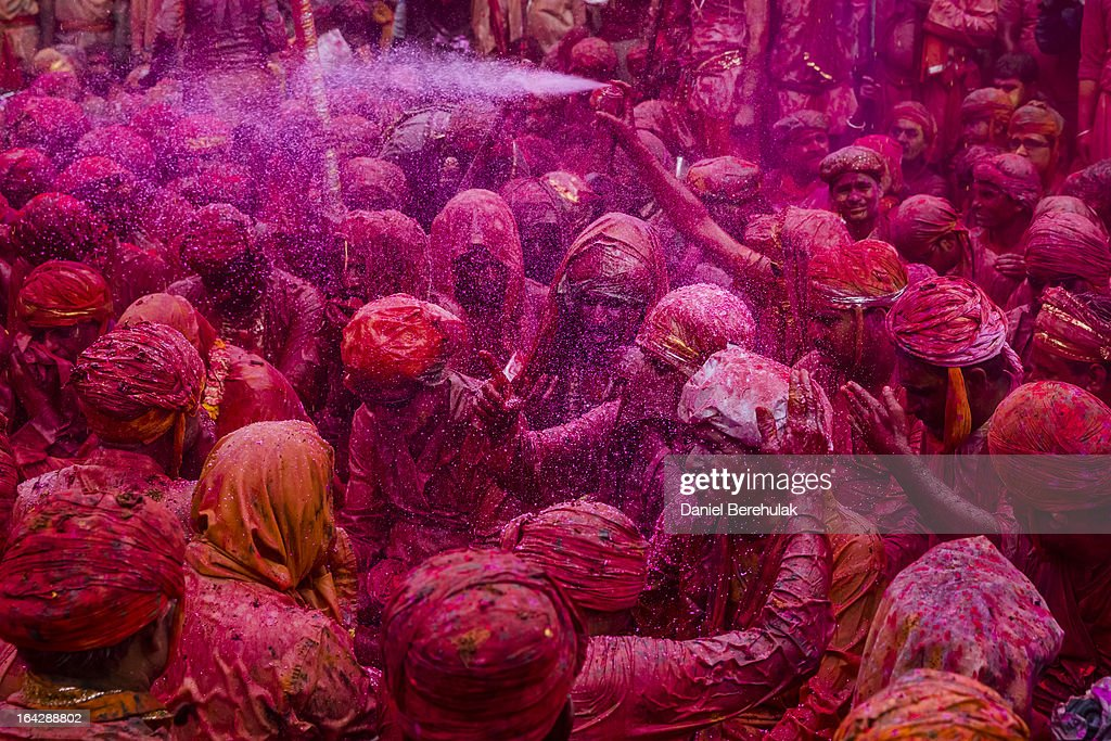 Villagers sing songs and play with color during Lathmaar Holi celebrations on March 22, 2013 in the village of Nundgaon near Mathura, India. The tradition of playing with colours on Holi draws its roots from a legend of Radha and the Hindu God Krishna. It is believed that young Krishna was jealous of Radha's fair complexion since he himself was himself very dark. After questioning his mother Yashoda on the darkness of his complexion, Yashoda, teasingly asked him to color Radha's face in which ever color he wanted. In a mischievous mood, Krishna applied color on Radha's face. The tradition of applying color on one's beloved is being religiously followed until today.