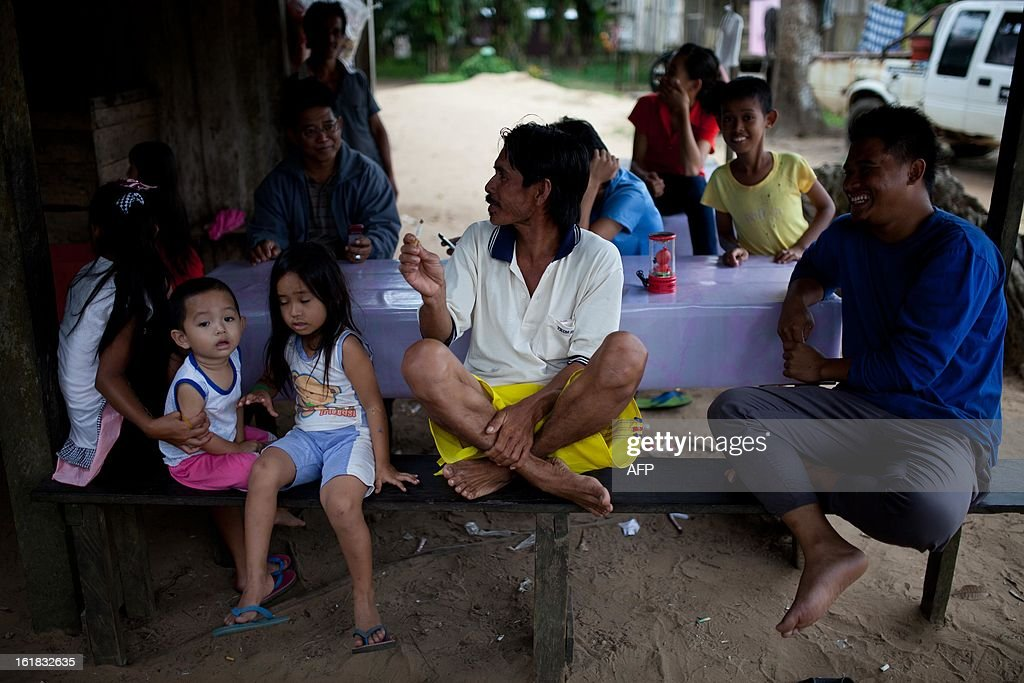 Villagers sit at a stall in Tanjung Labian in the area where suspected Philippine militants are holding off, near Lahad Datu on the Malaysian island of Borneo, on February 17, 2013. Malaysia's government said on February 14 that its security forces have surrounded dozens of suspected Philippine militants in a remote area with a history of incursions by armed Filipino Islamic groups.