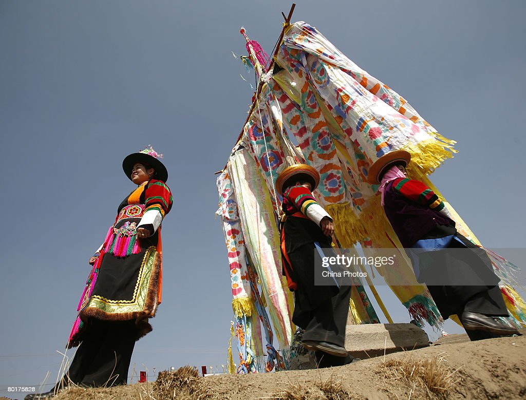 Villagers stand below Pray Flags during a ceremony to worship the Erlang God at the Dazhuang Village on March 9, 2008 in Huzhu County of Qinghai Province, China. The villagers believe that the Erlang God is their protector and they offer sacrifice to him annually on the second day of the second lunar month.