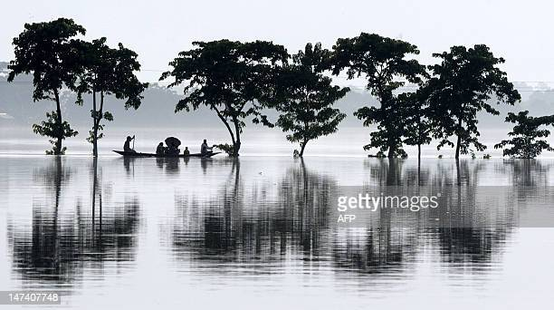 Villagers travel on a country boat through flood waters at the flood affected area of Tataliguri in Morigoan district some 80 kms from Guwahati the...