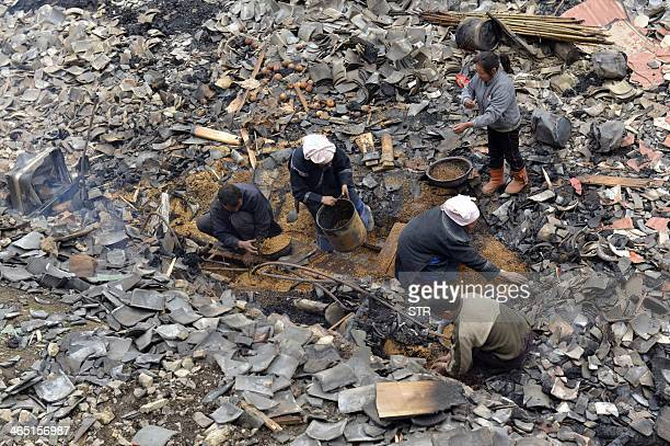 Villagers try to salvage whatever remains at Baojing Dong village in Guizhou province on January 26 2014 after a fire broke out late January 25 that...
