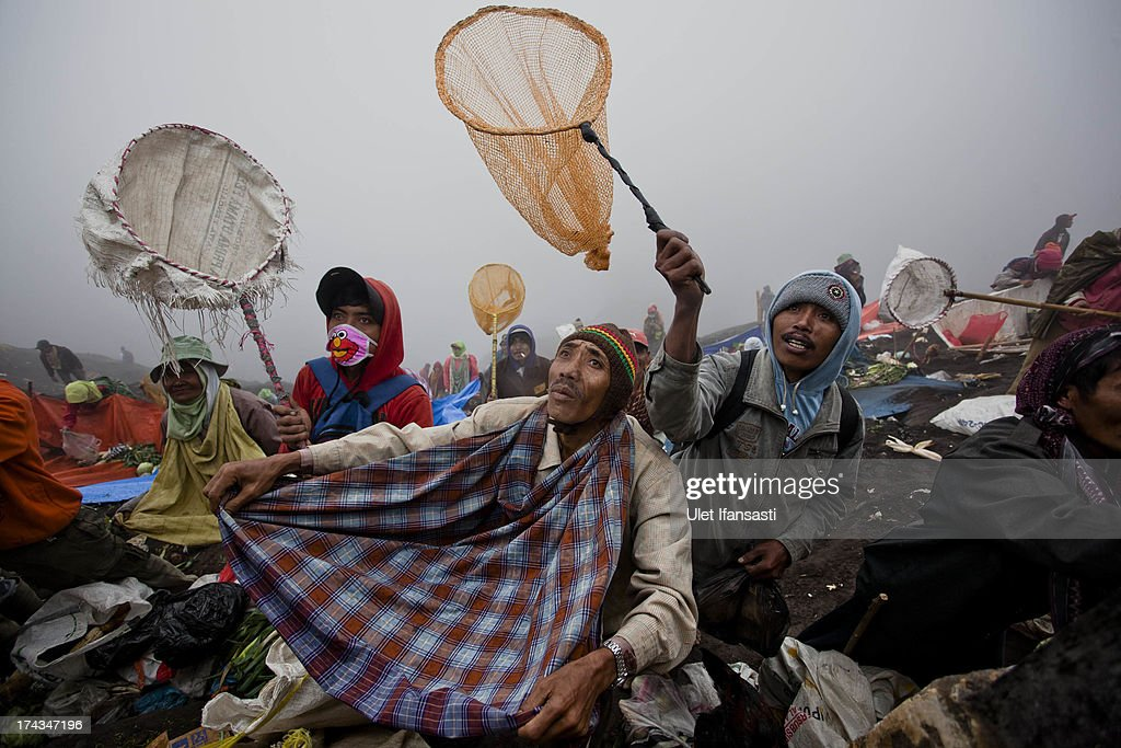 Villagers use nets and sarong as waits to catch offerings thrown by Hindu worshippers at the crater of Mount Bromo during the Yadnya Kasada Festival at crater of Mount Bromo on July 24, 2013 in Probolinggo, East Java, Indonesia. The festival is the main festival of the Tenggerese people and lasts about a month. On the fourteenth day, the Tenggerese make the journey to Mount Bromo to make offerings of rice, fruits, vegetables, flowers and livestock to the mountain gods by throwing them into the volcano's caldera. The origin of the festival lies in the 15th century when a princess named Roro Anteng started the principality of Tengger with her husband Joko Seger, and the childless couple asked the mountain Gods for help in bearing children. The legend says the Gods granted them 24 children but on the provision that the 25th must be tossed into the volcano in sacrifice. The 25th child, Kesuma, was finally sacrificed in this way after initial refusal, and the tradition of throwing sacrifices into the caldera to appease the mountain Gods continues today.