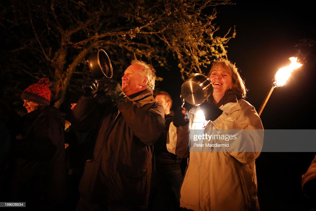 Villagers use saucepans to make a noise in the 'general hullabaloo', part of the Apple Howling ceremony at Old Mill Farm on January 5, 2013 in Bolney, England. In this ancient ritual villagers surround the oldest and largest tree in the orchard and evil spirits are driven out and good spirits are encouraged to produce a bountiful apple crop for the following year's cider drink.