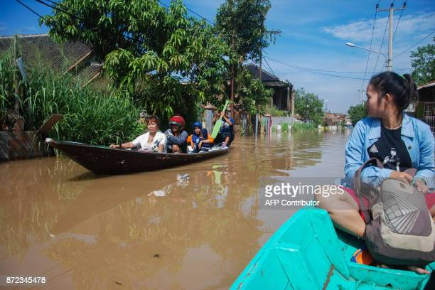 Villagers use wooden boats to travel along a flooded road in Bale Endah village in Bandung West Java on November 10 2017 Landslides and flooding are...