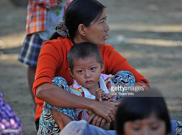 Villagers victims of recent earthquake sit on the ground in Sintgu township Mandalay a division in central Myanmar on November 12 2012 Rescuers in...