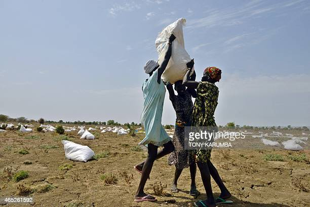 Villagers volunteer to carry sacks of food aid from a field following an airdrop at a village in Nyal an administrative hub of Panyijar county in...