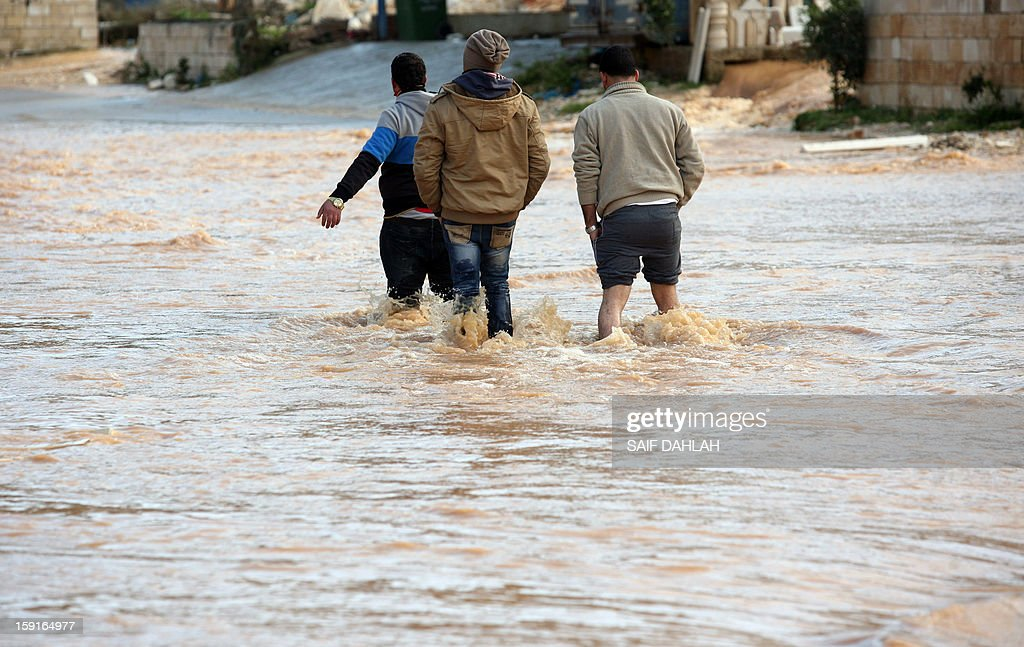 Villagers wade through flood waters in the village of Qabatiya, in the Israeli occupied West Bank near the northern city of Jenin, on January 9, 2013, as rain and snow engulfs the Levant.