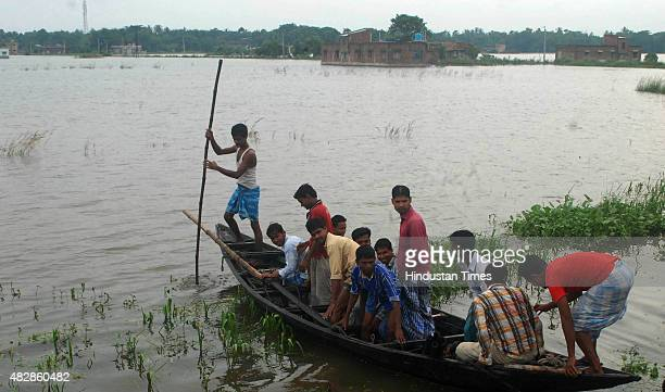 Villagers wade through flood waters on boats at Howrah's flood affected area Amta Chandra Pur on August 3 2015 in Kolkata India Death toll mounted to...