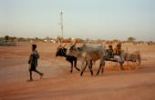 Villagers walk by an Exxon Mobil rig at Kome The pipeline will carry oil from the landlocked oil fields of Chad through the jungles of Cameroon to...