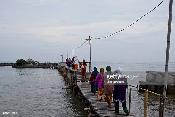 Villagers walk over the bridge to ancestral graves flooded from rising sea levels in Bedono village on December 12 2013 in Demak Central Java...