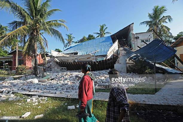 Villagers walk past a damaged monastery in Sintgu township Mandalay a division in central Myanmar on November 12 2012 Rescuers in Myanmar struggled...