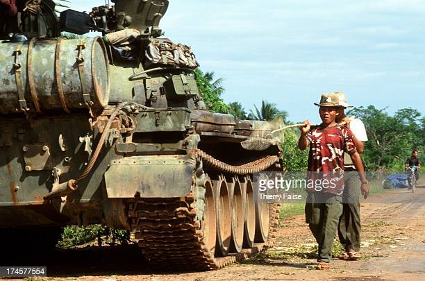 Villagers walk past a tank during the 1997 coup d'etat on the road from Siem Reap to Sisophon